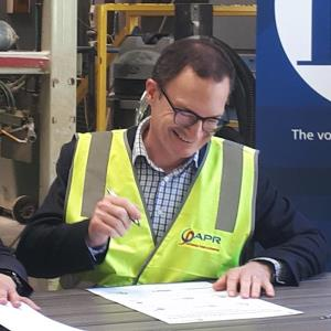 AHC CEO Andrew Aitken signs the agreement